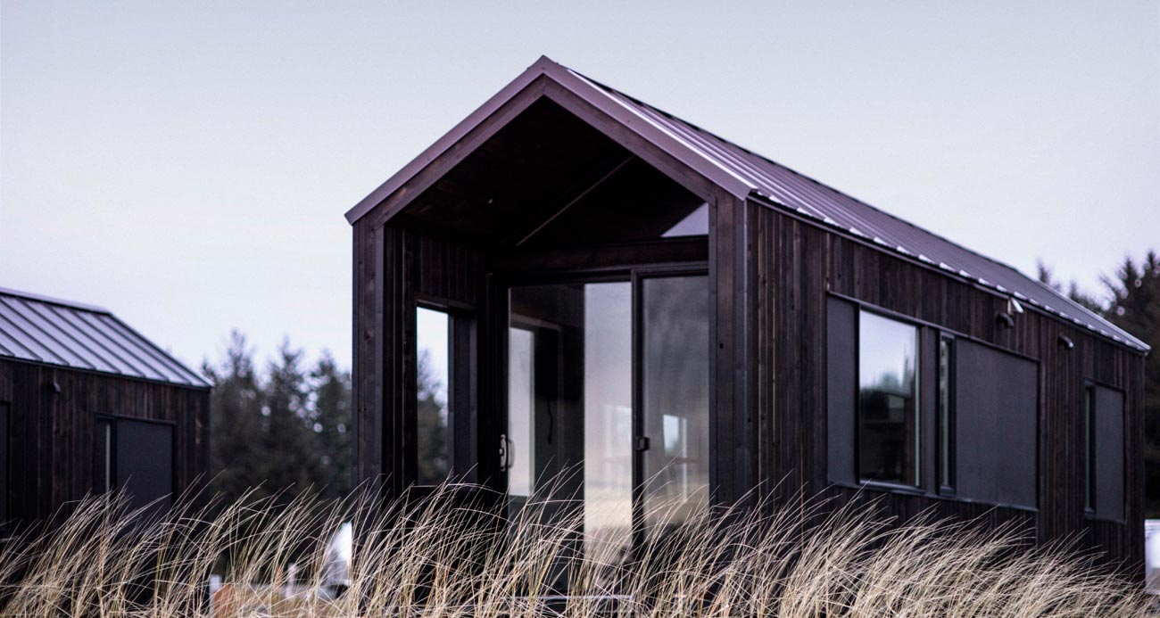 view of front of kamp haus cabin over blades of grass