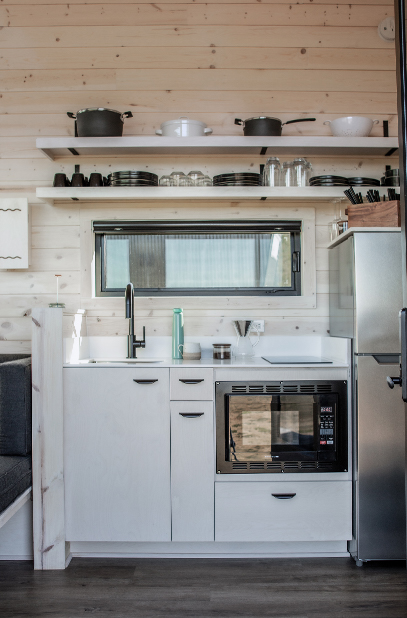 A modern kitchenette complete with a sink, microwave, refrigerator, and dishes.