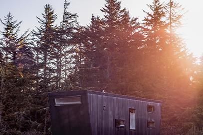 A black, modern Dune cabin at sunset.